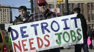 "Chrysler Transport worker Theisen carries a ""Detroit Needs Jobs"" sign as he joins a demonstration demanding jobs in Detroit"