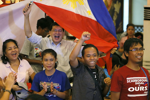 "Filipinos applaud moments after the Hague-based UN international arbitration tribunal ruled in favor of the Philippines in its case against China on the dispute in South China Sea Tuesday, July 12, 2016 in Manila, Philippines. The tribunal has found that there is no legal basis for China's ""nine-dash line"" claiming rights to much of the South China Sea. The tribunal issued its ruling Tuesday in The Hague in response to an arbitration case brought by the Philippines against China. (AP Photo/Bullit Marquez)"